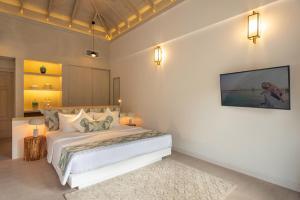 A bed or beds in a room at Bandos Maldives