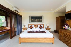 Een bed of bedden in een kamer bij Alamdini Resort Ubud