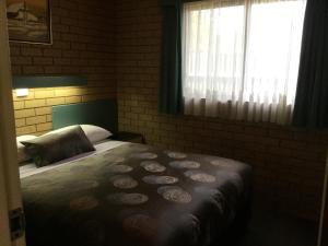 A bed or beds in a room at Sunrise Motel
