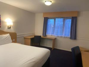 A bed or beds in a room at Days Inn Michaelwood M5