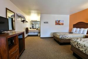 A bed or beds in a room at Adventure Inn Moab