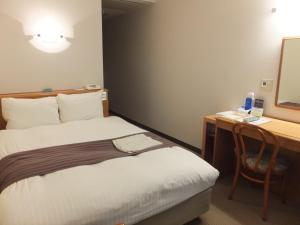 A bed or beds in a room at Tottori City Hotel