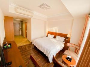 A bed or beds in a room at Woodpecker Suites & Hotels