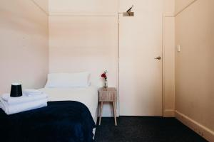 A bed or beds in a room at Port Macquarie Hotel