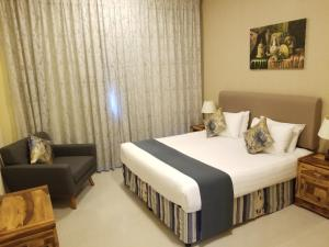 A bed or beds in a room at Ewan Tower Hotel Apartments