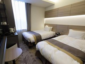 A bed or beds in a room at Nihon Seinenkan Hotel