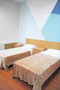 A bed or beds in a room at Olimpia Mini Hotel