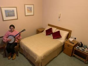 A bed or beds in a room at Rathbaun Hotel