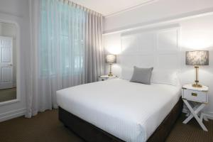 A bed or beds in a room at Adina Apartment Hotel Brisbane Anzac Square