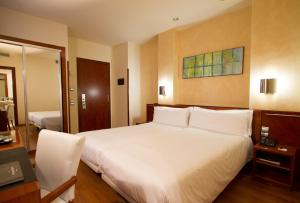 A bed or beds in a room at Hotel Garbi Millenni