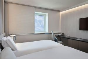 A bed or beds in a room at Sofitel Athens Airport