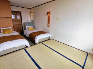 A bed or beds in a room at Fujio Pension Madarao