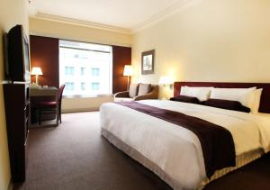 A bed or beds in a room at Prudential Hotel
