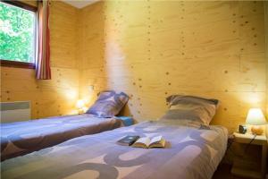 A bed or beds in a room at Villages de Gîtes des Châtaigniers du Lac