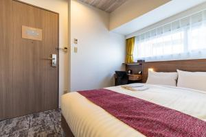 A bed or beds in a room at Nishitetsu Inn Kamata