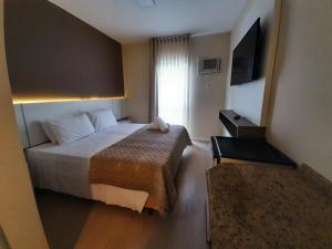 Cama ou camas em um quarto em Caravaggio Praia Hotel
