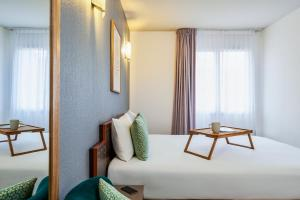 A bed or beds in a room at Aparthotel Adagio Access Nice Acropolis
