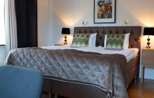 A bed or beds in a room at Mjölby Stadshotell
