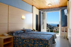 A bed or beds in a room at Hotel Grecs