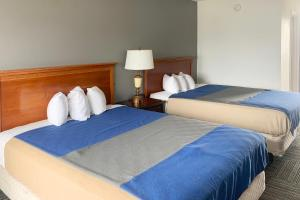 A bed or beds in a room at OYO Hotel Lake St Louis