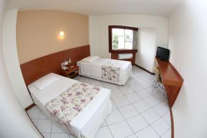 A bed or beds in a room at Hotel Caiuá