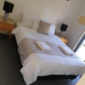 A bed or beds in a room at Madigan Wine Country Cottages