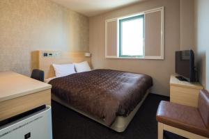 A bed or beds in a room at Sanco Inn Nagoya - Shinkansenguchi