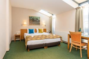 A bed or beds in a room at Euterpe Hotel