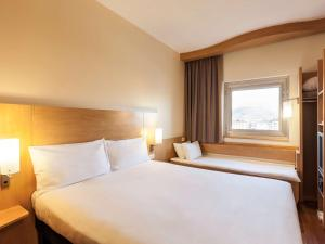 A bed or beds in a room at ibis London Luton Airport