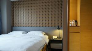A bed or beds in a room at City Suites - Taoyuan Gateway