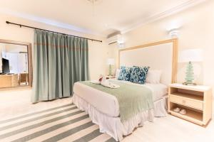 A bed or beds in a room at Bay Gardens Beach Resort