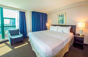 A bed or beds in a room at Rosedale on Robson Suite Hotel