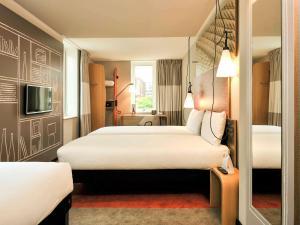 سرير أو أسرّة في غرفة في إيبيس روتردام سيتي سنتر