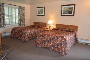 A bed or beds in a room at The Village Motel
