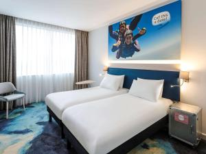 A bed or beds in a room at ibis Styles London Heathrow Airport
