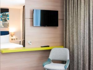 A television and/or entertainment centre at ibis Styles London Heathrow Airport