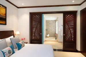 A bed or beds in a room at Anantara Hoi An Resort