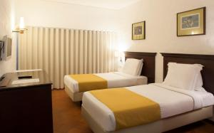 A bed or beds in a room at Hotel do Mar