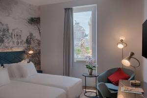 A bed or beds in a room at NH Collection Roma Fori Imperiali