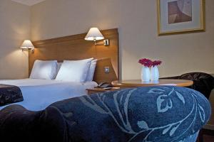 A bed or beds in a room at Hickstead Hotel