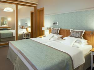 A bed or beds in a room at Travel Charme Kurhaus Binz