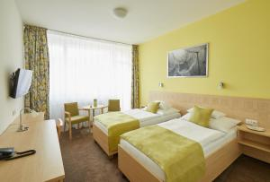 A bed or beds in a room at Hotel Běhounek