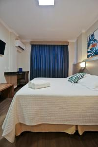 A bed or beds in a room at Sandri City Hotel