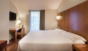 A bed or beds in a room at NH Zamora Palacio del Duero