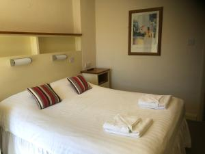 A bed or beds in a room at The Brotherswater Inn