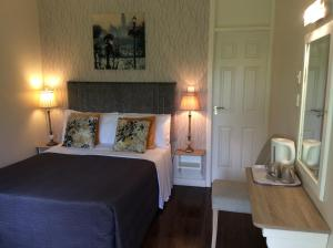 A bed or beds in a room at The Gardens B&B