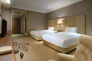 A bed or beds in a room at LIXIN Grand Hotel
