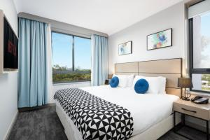 A bed or beds in a room at Quest North Ryde