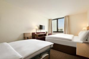 A bed or beds in a room at Ramada Nürnberg Parkhotel