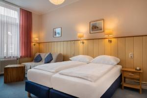 A bed or beds in a room at Hotel Stadt Lübeck